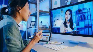 Asia empresaria que usa el escritorio hablar con sus colegas sobre el plan en la reunión de videollamada en la sala de estar. trabajando desde casa por sobrecarga nocturna, trabajo a distancia, distanciamiento social, cuarentena por coronavirus. foto