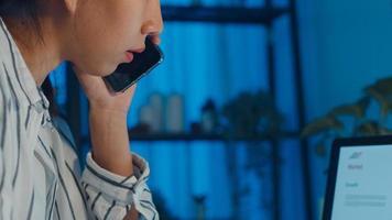 joven empleada asiática trabaja horas extras tarde en la noche estrés finanzas investigación de proyectos de contabilidad en la computadora portátil en casa. la estudiante aprende en línea en la casa, la distancia social, el nuevo trabajo normal desde el concepto de hogar. foto