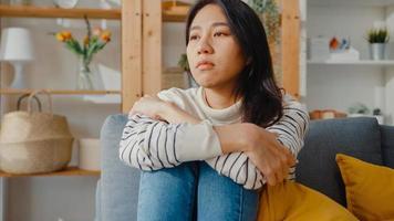 pensativa dama asiática sentada abrazándose de rodillas en el sofá en la sala de estar en la casa mirar afuera con sentirse solo, triste adolescente deprimido pasar tiempo solo quedarse en casa, distancia social, cuarentena de coronavirus. foto