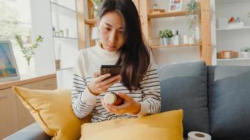 mujer asiática joven enferma mantenga la medicina sentarse en el sofá tomar una foto enviada al médico en casa. chica toma medicamentos después de la orden del médico, cuarentena en casa, concepto de cuarentena de distanciamiento social de coronavirus.