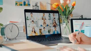 Young asia female employee listen leader on video call with diverse multiracial colleagues on online with laptop at home. Distance learning. Girl student learn online at house, Online meeting concept. photo