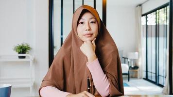 Asia dama musulmana usa hijab usando computadora portátil, hable con colegas sobre el plan en una reunión de videollamada mientras trabaja de forma remota desde su casa en la sala de estar. distanciamiento social, cuarentena por coronavirus. foto