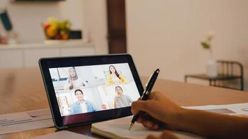 Asia empresaria que usa tableta digital habla con un colega sobre el plan mediante videollamada para intercambiar ideas sobre una reunión en línea mientras trabaja de forma remota desde casa en la cocina. distanciamiento social, cuarentena por coronavirus. foto