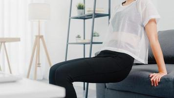 Joven coreana en ejercicios de ropa deportiva haciendo ejercicio haciendo tríceps apoyado en el sofá en la sala de estar en casa. distancia social, aislamiento durante el virus. ejercicios para la parte inferior del cuerpo. foto