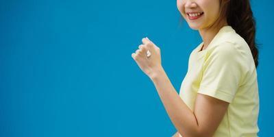 joven asiática aplicando crema protectora en las manos aisladas sobre fondo azul. Copie el espacio para colocar un mensaje de texto, para publicidad. área publicitaria, maqueta de contenido promocional. foto