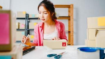 Young Asia entrepreneur businesswoman check product purchase order on stock and save to tablet computer work at home office. Small business owner, online market delivery, lifestyle freelance concept. photo