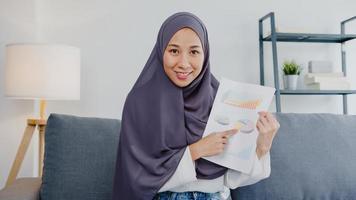 Asia dama musulmana usa hijab, usa computadora portátil, habla con colegas sobre el informe de venta en una reunión de videoconferencia mientras trabaja de forma remota desde casa en la sala de estar. distanciamiento social, cuarentena por coronavirus. foto