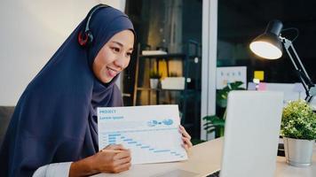 Asia dama musulmana usa auriculares usando una computadora portátil, hable con sus colegas sobre el informe de venta en una videoconferencia mientras trabaja desde la oficina en casa por la noche. distanciamiento social, cuarentena por coronavirus. foto