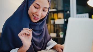 hermosa dama musulmana de asia en ropa casual con pañuelo en la cabeza usando la computadora portátil en la sala de estar en la casa de noche. trabajo a distancia desde casa, nuevo estilo de vida normal, distancia social, cuarentena para la prevención del virus corona. foto
