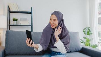 Asia dama musulmana usa hijab usando videollamada telefónica hablando con pareja en casa. joven adolescente haciendo video de vlog en las redes sociales en el sofá de la sala de estar. distanciamiento social, cuarentena por coronavirus. foto