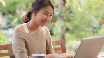 mujer asiática independiente que trabaja en casa, mujer de negocios que trabaja en la computadora portátil sentada en la mesa en el jardín por la mañana. mujeres de estilo de vida que trabajan en el concepto de hogar. foto