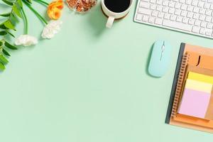 espacio de trabajo mínimo: foto creativa plana del escritorio del espacio de trabajo. escritorio de oficina de vista superior con teclado, mouse y cuaderno sobre fondo de color verde pastel. vista superior con espacio de copia, fotografía plana.