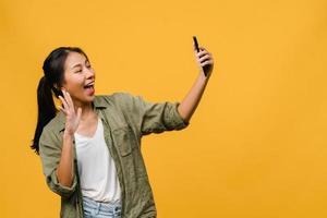Sonriente mujer asiática adorable haciendo foto selfie en teléfono inteligente con expresión positiva en ropa casual y soporte aislado sobre fondo amarillo. feliz adorable mujer alegre se regocija con el éxito.