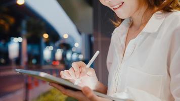 Exitosa empresaria asiática joven en ropa de oficina de moda utilizando tecnología de lápiz inteligente para escribir en tableta digital mientras se sienta sola al aire libre en la ciudad moderna urbana por la noche. concepto de negocio en movimiento. foto