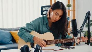 Happy asia woman songwriter play acoustic guitar listen song from smartphone think and write notes lyrics song in paper sit in living room at home studio. Music production at home concept. photo