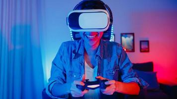 Happy young asia girl gamer winner wear virtual reality glasses goggles headset and joystick controller fun and excited with online game in neon home studio at night, Home quarantine activity. photo