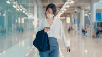 Chica de negocios asiática usa un teléfono inteligente para registrar la tarjeta de embarque y camina con el equipaje a la terminal del vuelo nacional en el aeropuerto. pandemia de covid viajero de negocios, concepto de distanciamiento social de viajes de negocios. foto