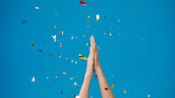 niña muestra la mano aplaudiendo aplausos bajo la lluvia de confeti y celebrando sobre fondo azul. Copie el espacio para colocar un mensaje de texto, para publicidad. área publicitaria, simulacro de contenido promocional. foto
