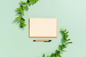 Foto creativa plana del escritorio del espacio de trabajo. Escritorio de oficina de vista superior con maquetas abiertas de cuadernos en blanco y lápiz y planta sobre fondo de color verde pastel. vista superior con maqueta de fotografía de espacio de copia.