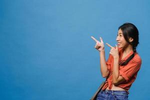 Retrato de joven asiática sonriendo con expresión alegre, muestra algo sorprendente en el espacio en blanco en ropa casual y de pie aislado sobre fondo azul. concepto de expresión facial. foto