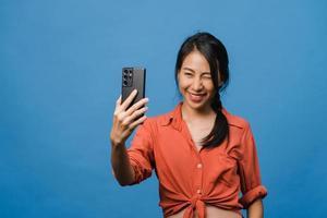 Sonriente mujer asiática adorable haciendo foto selfie en teléfono inteligente con expresión positiva en ropa casual y soporte aislado sobre fondo azul. feliz adorable mujer alegre se regocija con el éxito.