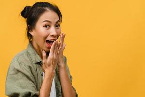 La joven asiática siente felicidad con expresión positiva, alegre sorpresa funky, vestida con ropa informal y mirando a cámara aislada sobre fondo amarillo. feliz adorable mujer alegre se regocija con el éxito. foto