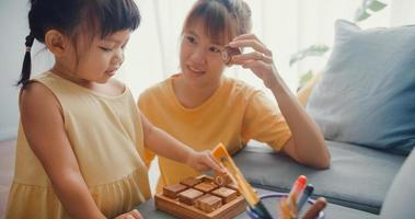 Happy cheerful Asia family mom teach girl play board game hobby with wooden box having fun relax on couch in living room at house. Spending time together, Social distance, Quarantine for coronavirus. photo