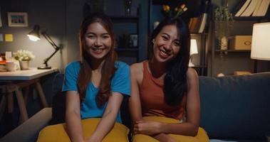 Teenager Asia women feeling happy smiling and looking to camera while relax in living room at home night. Cheerful Roommate ladies video call with friend and family, Lifestyle woman at home concept. photo