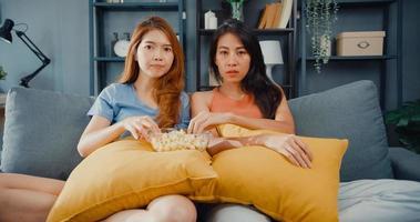 Asia atractiva pareja encantadora dama positiva alegre alegre con casual diviértase y disfrute el momento, vea el entretenimiento de películas en línea en el sofá de la sala de estar en casa. concepto de cuarentena de actividad de estilo de vida. foto