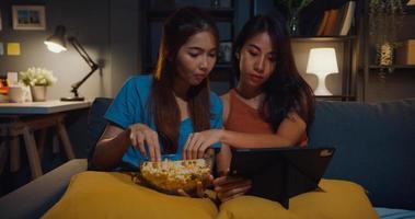 atractivas damas asiáticas con casual disfrutan de un momento feliz, miran entretenimiento de películas en línea en una tableta, comen un sitio de palomitas de maíz en el sofá, sala de estar en casa por la noche. concepto de cuarentena de actividad de estilo de vida. foto