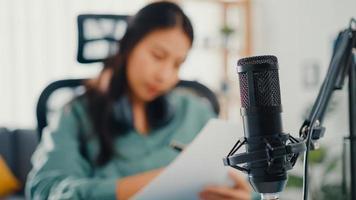 atractivo podcast de registro de niña de asia utiliza el micrófono sostenga el papel creando contenido para la charla de audio del blog y la práctica para el tema de revisión en su habitación. hacer podcast de audio desde casa, concepto de equipo de sonido. foto