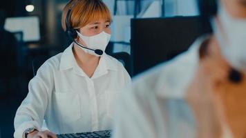 El equipo del centro de llamadas de jóvenes milenarios de Asia o el ejecutivo de servicio de atención al cliente que usan mascarilla evitan que el covid-19 use el soporte técnico de trabajo de auriculares con computadora y micrófono en la oficina nocturna. foto