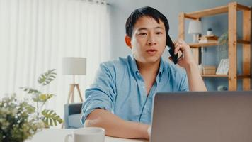 Freelance Asia guy casual wear using laptop talk on cell phone in living room at house. Working from home, remotely work, distance education, social distancing, quarantine for corona virus prevention. photo