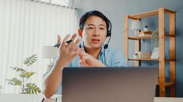 Young Asia businessman wear headphones using laptop talk to colleagues about plan in video call while work from home at living room. Self-isolation, social distancing, quarantine for covid prevention. photo