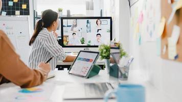 Los empresarios asiáticos que usan el escritorio hablan con sus colegas que discuten una lluvia de ideas sobre el plan en una reunión de videollamada en la nueva oficina normal. distanciamiento social de estilo de vida y trabajo después del virus corona. foto