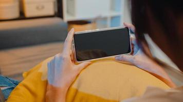 Joven mujer asiática usa un teléfono inteligente con pantalla negra en blanco simulada para mostrar texto publicitario mientras descansa en el sofá de la sala de estar en la moderna noche de casa. tecnología chroma key, concepto de diseño de marketing. foto