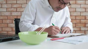 Thai man in white shirt uses chopsticks to eat hot instant noodles in green bowl in lunch breaks, quick, tasty, and cheap. Traditional Asian fast food meal of Japanese and Chinese lifestyle. video