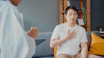 Joven mujer asiática médico profesional médico usando tableta digital compartiendo buenas noticias sobre pruebas de salud con paciente masculino feliz sentado en el sofá de la casa. seguro médico, visita al paciente en concepto de hogar. foto