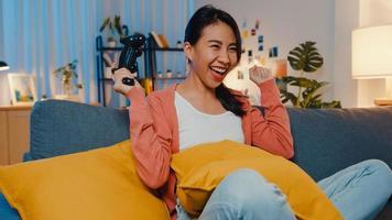 Jovencita asiática usando un controlador inalámbrico juega un videojuego que tiene un divertido momento feliz en el sofá de la sala de estar en casa por la noche. quedarse en casa, actividad de auto cuarentena para covid o cuarentena por coronavirus. foto