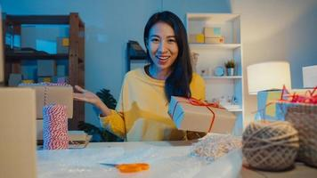 Happy young Asia businesswoman looking at camera selling  introduce product to client video live streaming in online shop  marketplace at night. Small business owner, online market delivery concept. photo