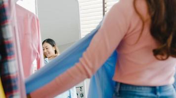 Bella dama atractiva de Asia eligiendo ropa en perchero vestirse mirando a sí misma en el espejo en el dormitorio en casa. chica piensa qué ponerse camisa casual. las mujeres de estilo de vida se relajan en el concepto de hogar. foto
