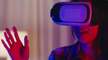 asia lady wear vr juego auriculares divirtiéndose experiencia usable virtual ar aumentada realidad digital innovación tecnología momento feliz año nuevo neón noche fiesta evento celebración en sala de estar en casa foto