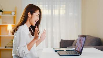 Mujer de negocios asiática joven que usa videollamada portátil hablando con papá y mamá de la familia mientras trabaja desde casa en la sala de estar. autoaislamiento, distanciamiento social, cuarentena para la prevención del coronavirus. foto