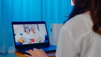 Asia estudiante de intercambio mujer usando una videollamada portátil hablando con la familia mientras trabaja desde casa en la sala de estar por la noche. autoaislamiento, distanciamiento social, cuarentena por coronavirus en la siguiente normalidad. foto