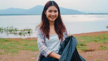 Portrait of young Asia lady volunteers help to keep nature clean up holding plastic bottle waste and black garbage bags on the beach. Concept about environmental conservation pollution problems. photo