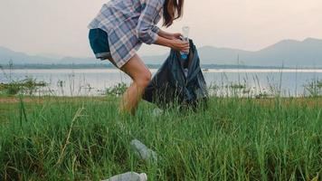 Happy young Asia activists collecting plastic waste on the beach. Korean lady volunteers help to keep nature clean up and pick up garbage. Concept about environmental conservation pollution problems. photo