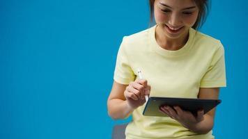 chica joven con tableta digital mirando el espacio vacío aislado sobre fondo azul. Copie el espacio para colocar un mensaje de texto, para publicidad. área publicitaria, maqueta de contenido promocional. foto