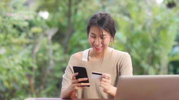 Mujer asiática con teléfono móvil y comercio electrónico de compras con tarjeta de crédito, mujer relajarse sintiéndose feliz de compras en línea sentado en la mesa en el jardín por la mañana. las mujeres de estilo de vida se relajan en el concepto de hogar. foto