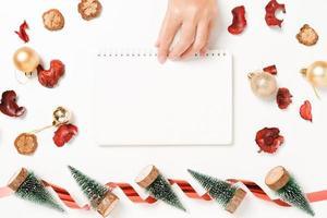 plano creativo mínimo de composición tradicional navideña de invierno y temporada navideña de año nuevo. vista superior abierta maqueta cuaderno negro para texto sobre fondo blanco. maqueta y copia la fotografía espacial. foto