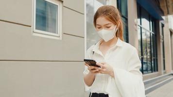 Exitosa empresaria asiática joven en ropa de oficina de moda con mascarilla médica con teléfono inteligente mientras camina solo al aire libre en la ciudad moderna urbana por la mañana. concepto de negocio en movimiento. foto